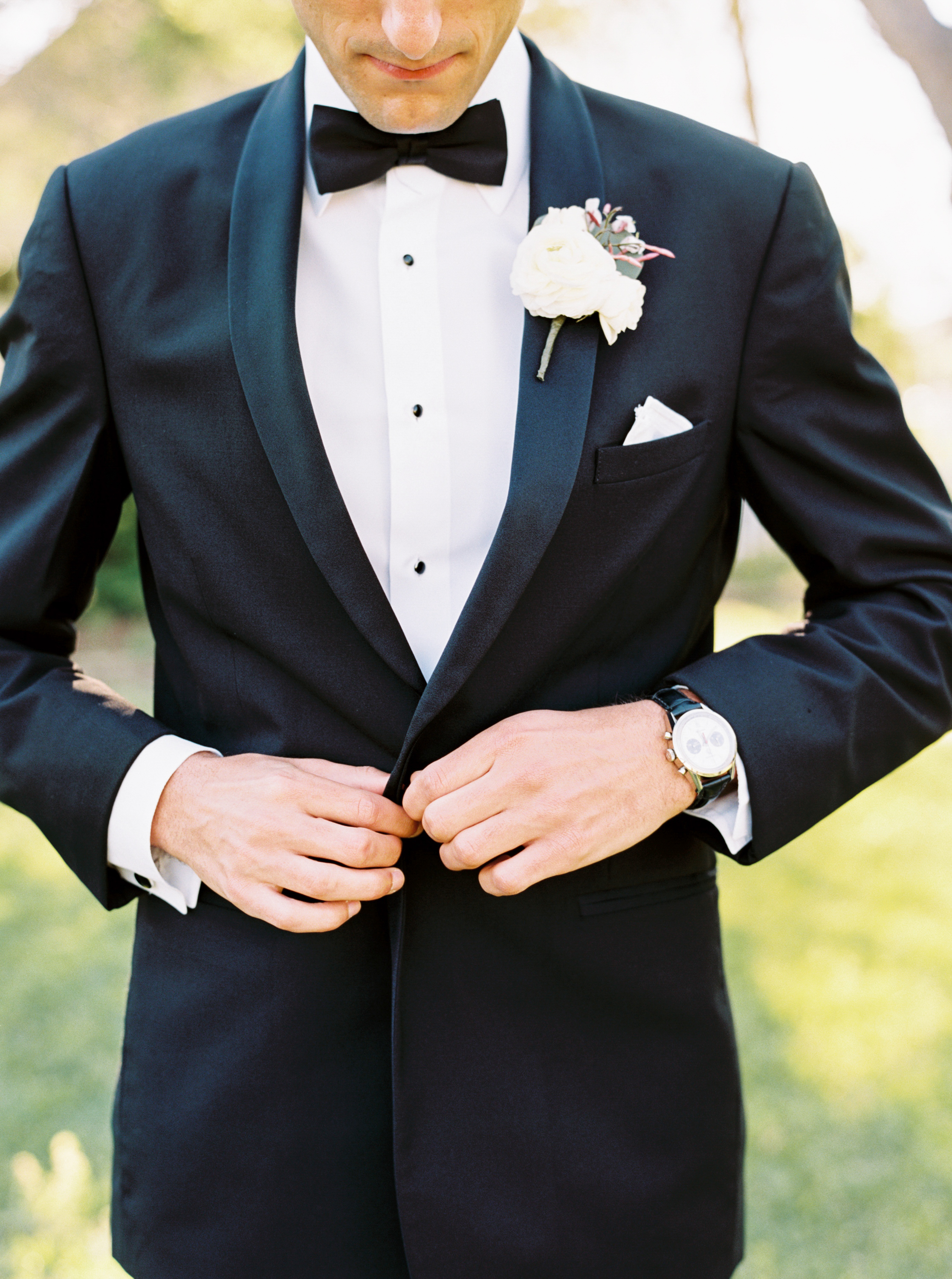 groom in black tux with boutonniere from maxit flower design in houston