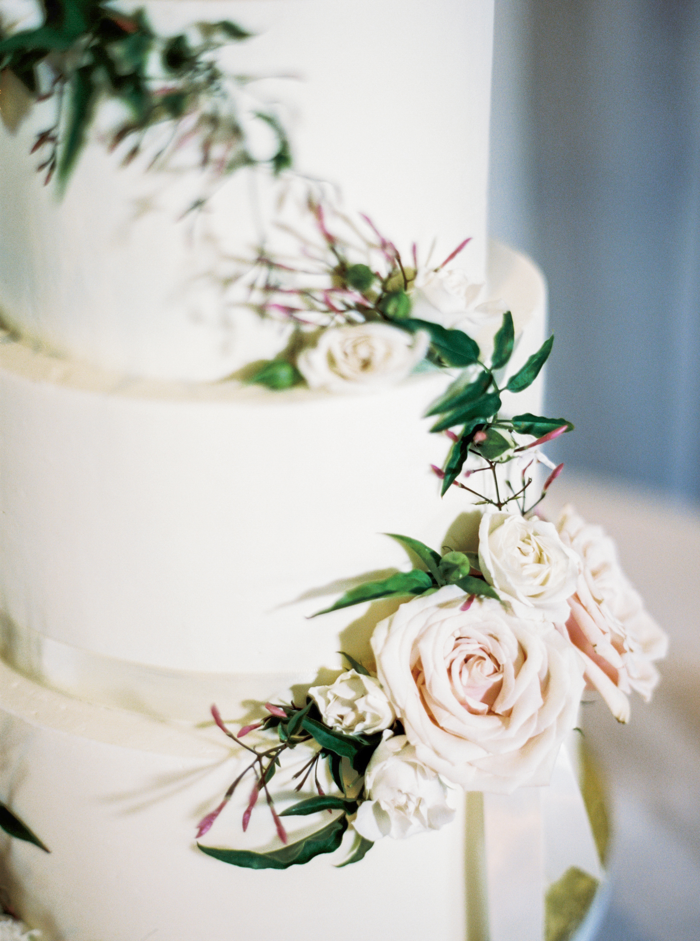 white wedding cake with greenery and blush roses by maxit flower design