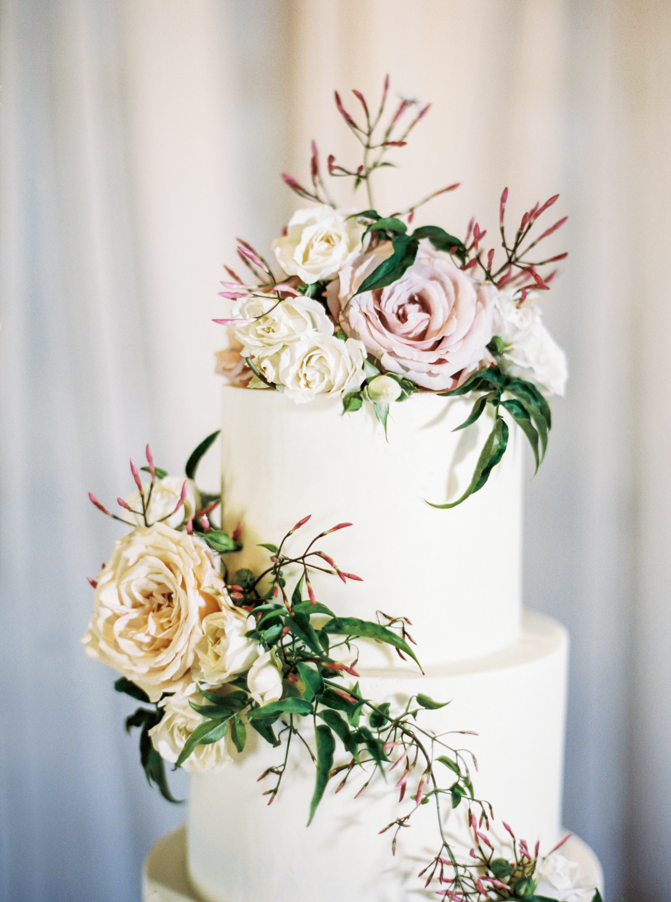 white cake with roses and greenery by maxit flower design in houston texas