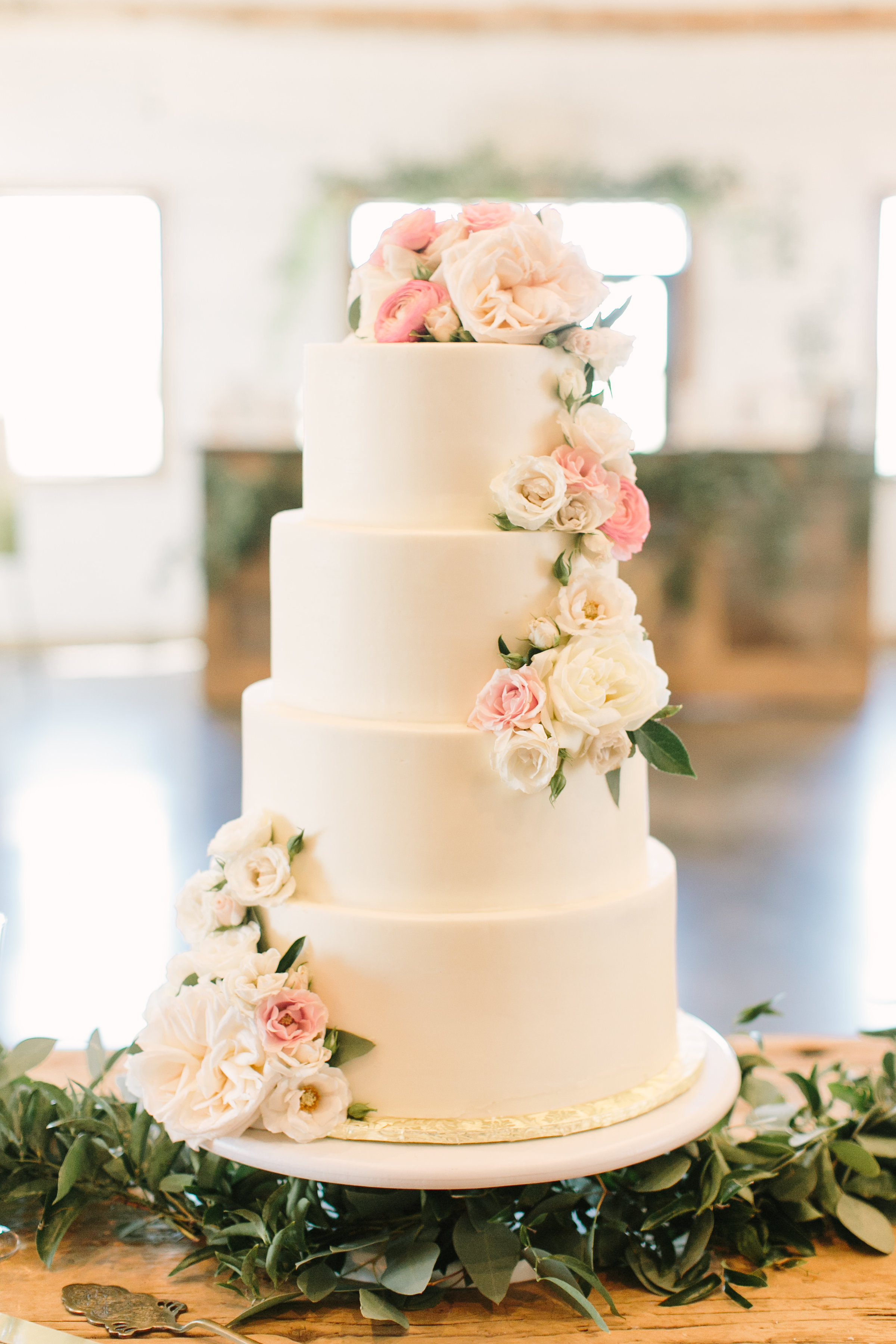 white wedding cake with blush florals and greenery by maxit flower design in houston texas