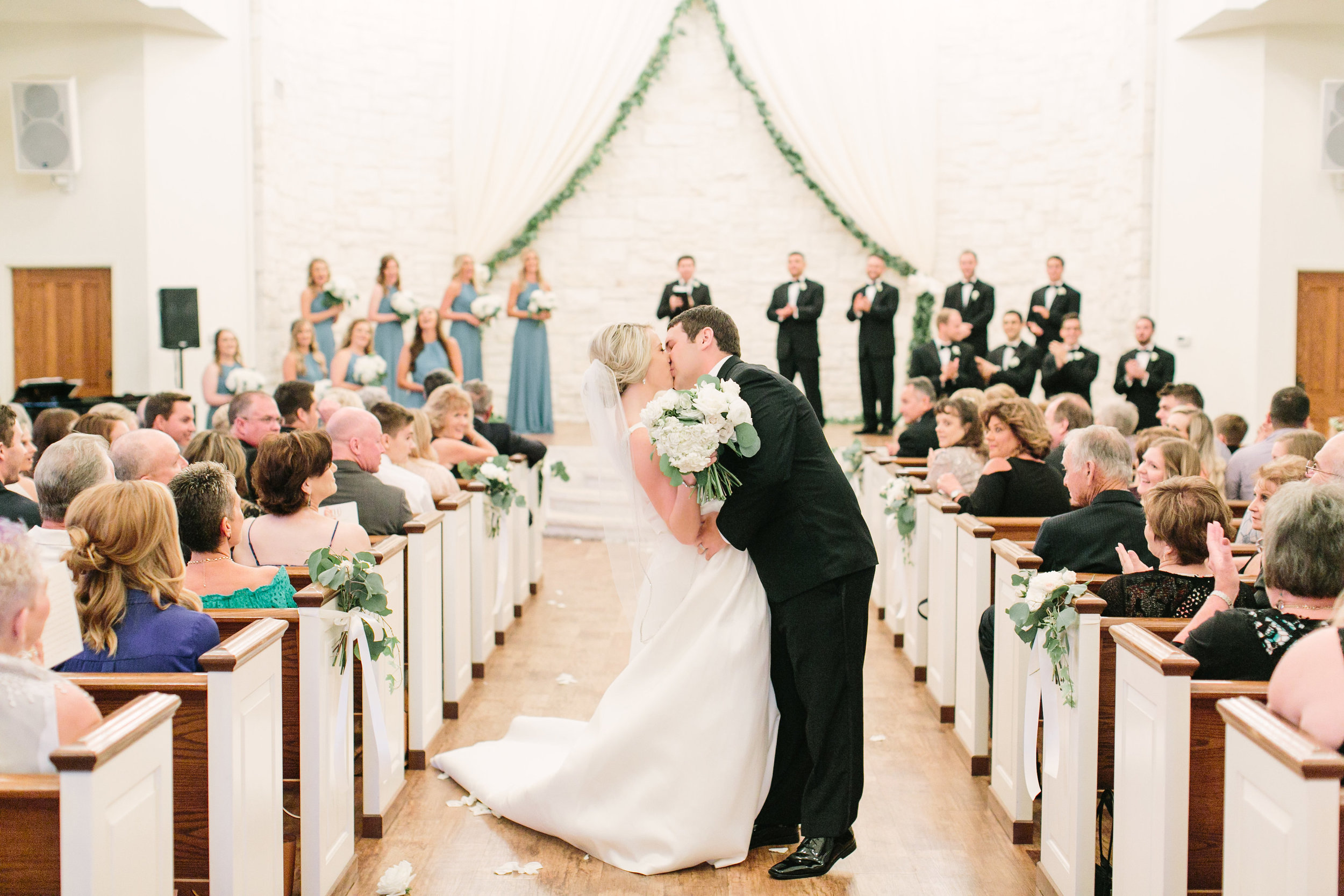 first-kiss-briscoe-manor-ceremony-bride-groom-white-bouquet-greenery-garland-by-maxit-flower-design-in-houston-texas
