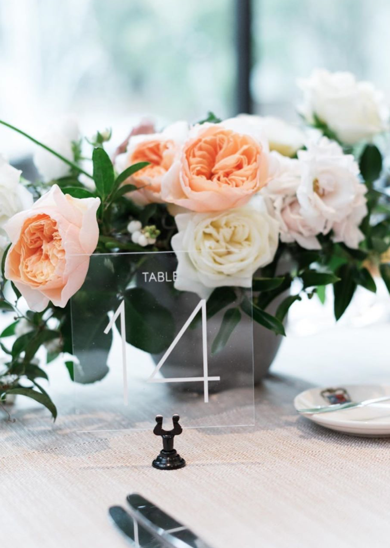 Modern table number made from acrylic. Yellow, white and blush colored flowers with garden roses and jasmine. Houston, Texas wedding in Rice University, Cohen House. Photographed by Josh & Dana Fernandez