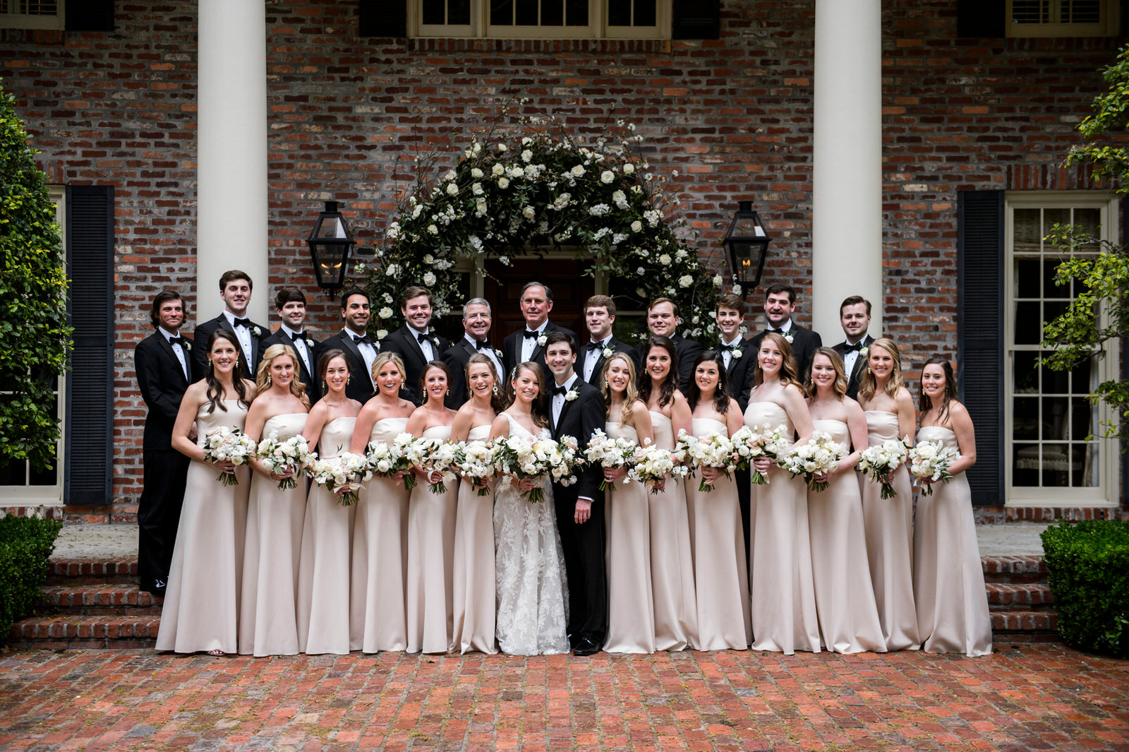Bride with bridesmaids and groom. Blush, white and green bouquets in a lush garden style. In front on brides family home with a floral arch. Houston, Texas. Maxit Flower Design,  Alyssa Meeks  ,  Chris Bailey Photography