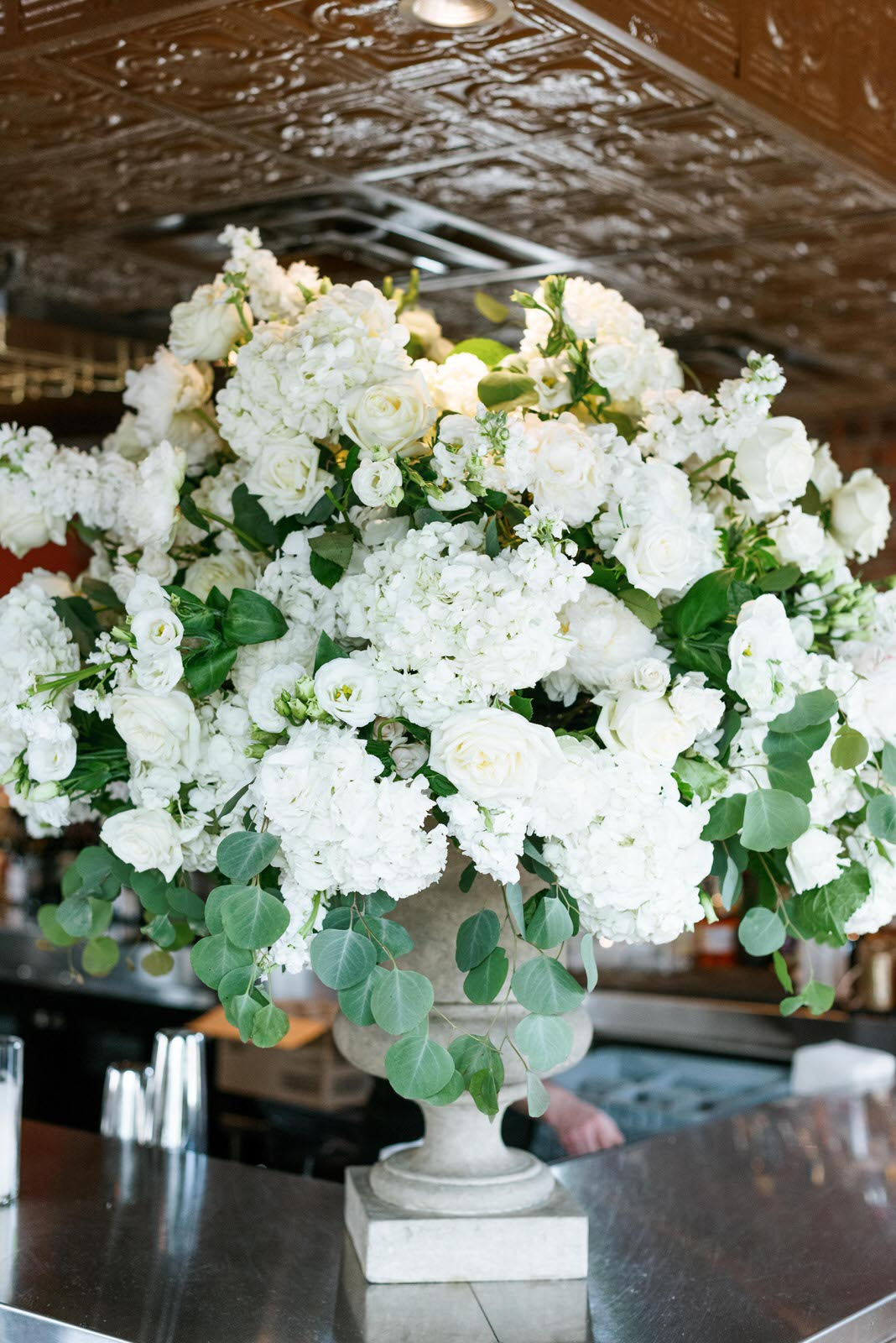White urn arrangement with lush florals, including hydrangea, roses, eucalyptus. Photography:  Josh & Dana Fernandez , Event Design & Floral:  Maxit Flower Design , Event Planner: Emily Moise,  Keely Thorne Events