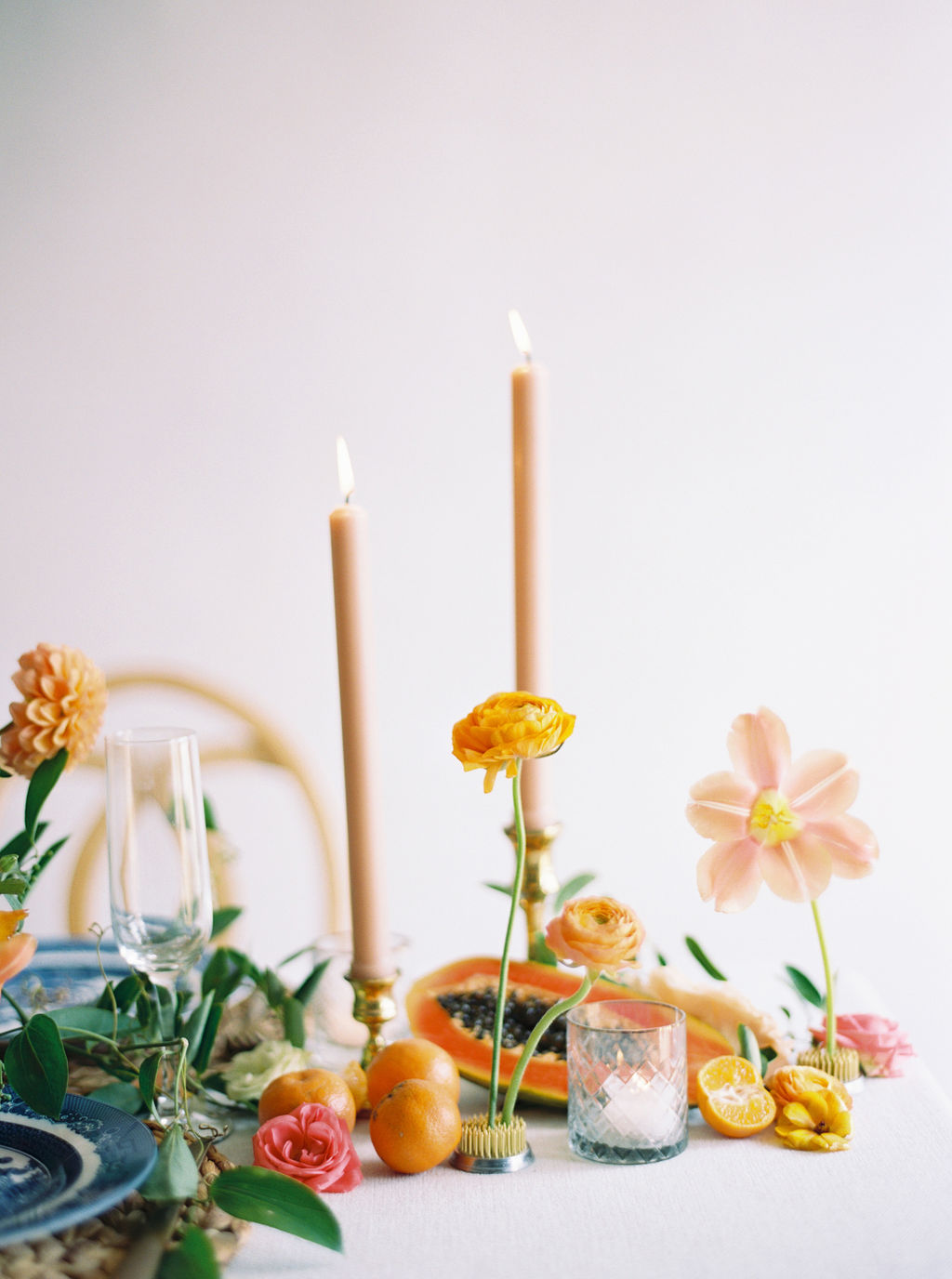 Summer soiree with a papaya inspired table scape. Taper candles and floral frogs as accents. Houston, TX. Floral & Event Design: Maxit Flower Design, Photography:  Courtney Leigh Photography