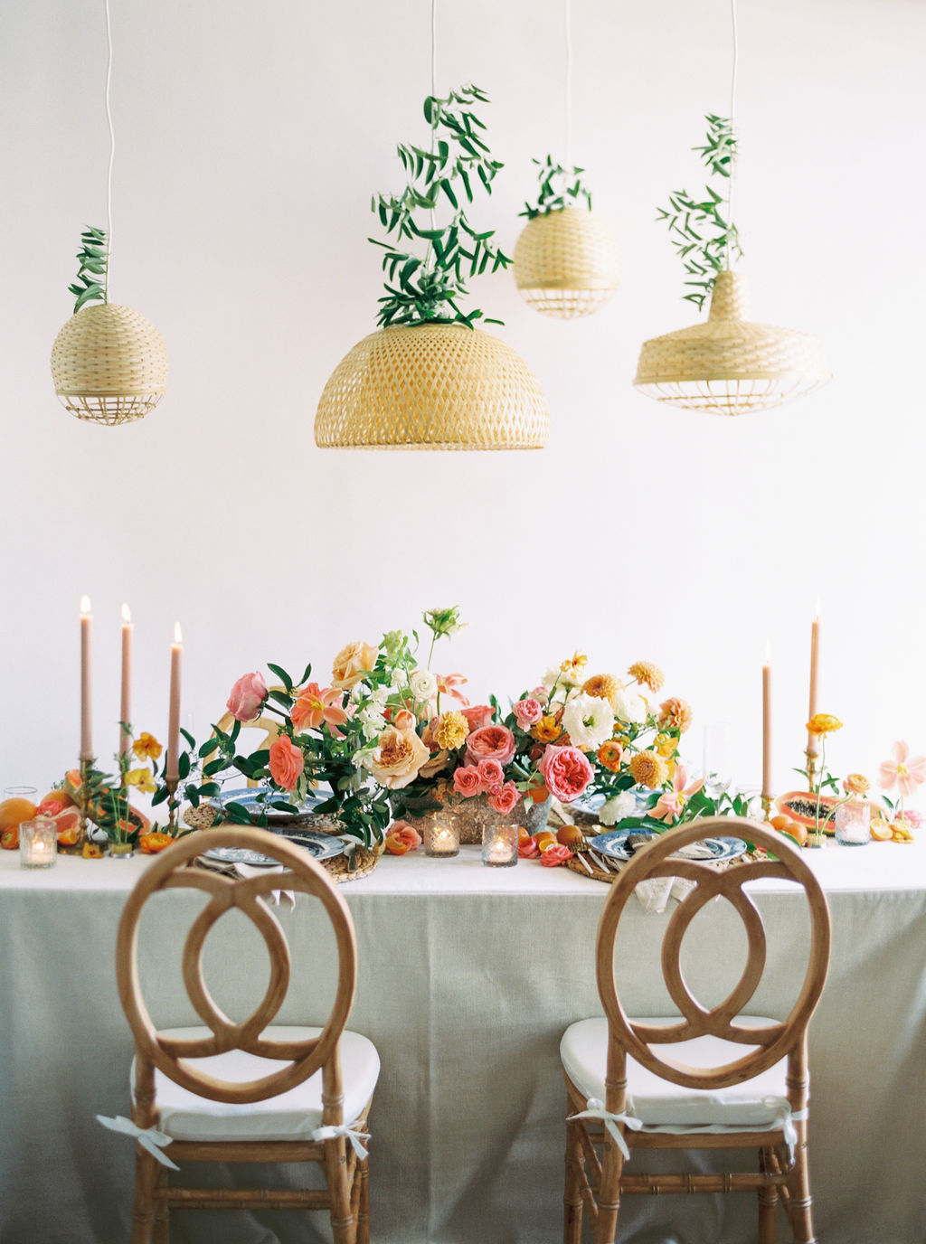 Rich blue linen with woven charger and white plate. Coral and papaya inspired color palette. Houston, TX. Floral & Event Design: Maxit Flower Design, Photography:  Courtney Leigh Photography  , Goblet: Flower Power Productions