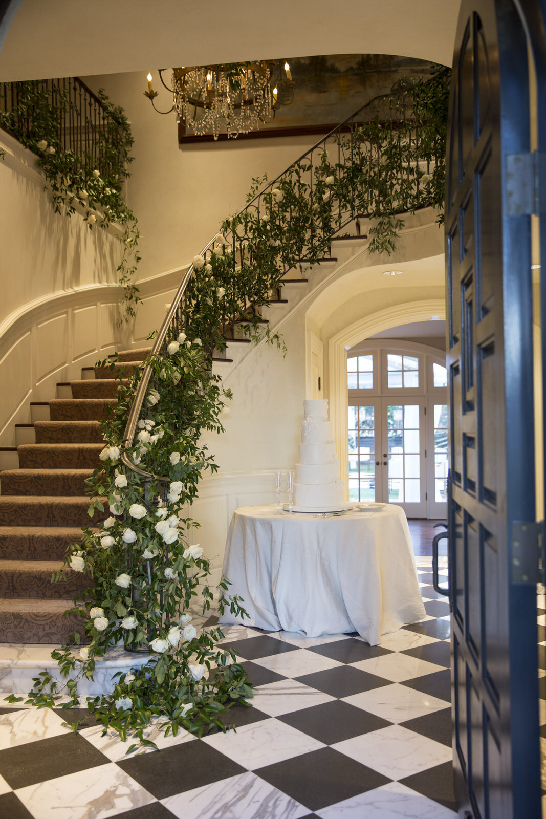 Smilax and florals on staircase with florals through out the cake, Houston, Texas wedding with Jennifer Kaldis of Keely Thorne Events. Maxit Flower Design.