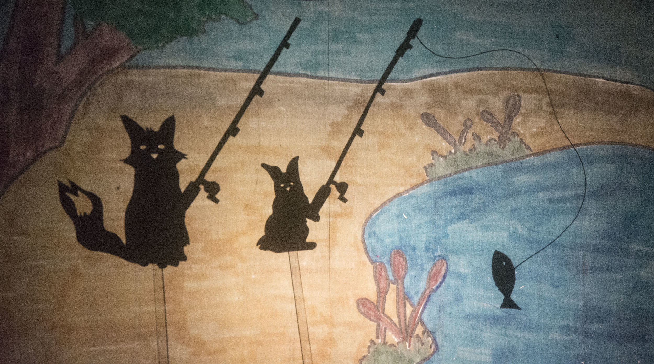 "fox & rabbit shadow puppets on a drawn overhead projector background created for the story ""why the fox hunts for food"" by danielle kayonnie, 3rd grade"