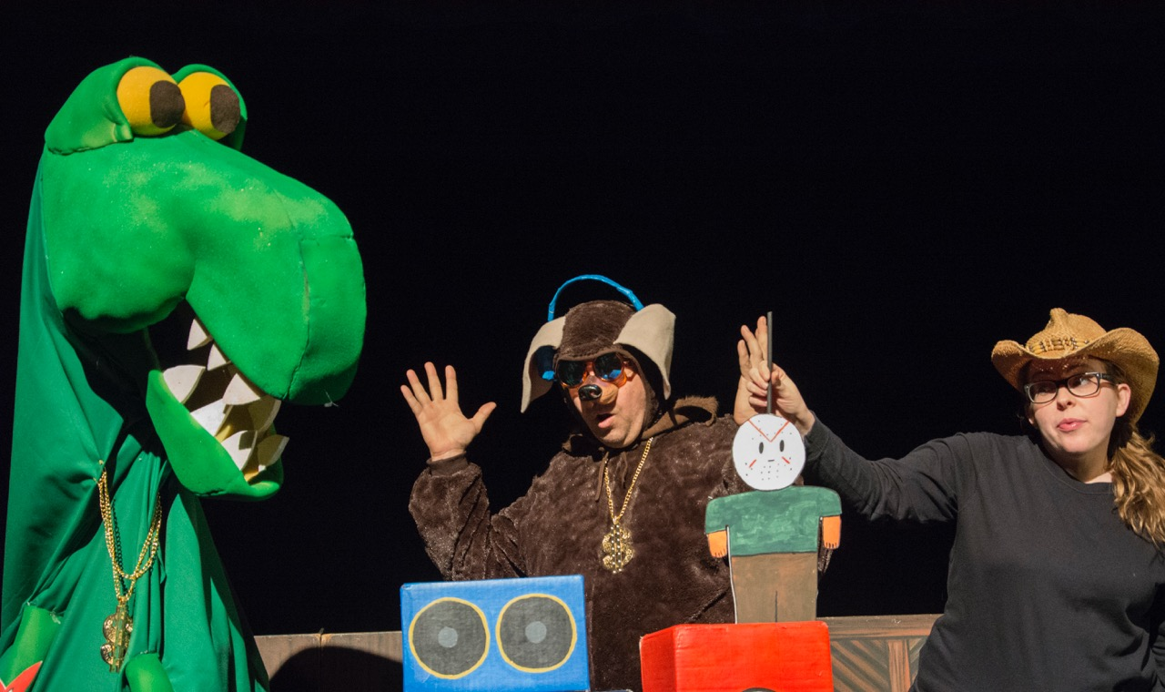 "action in ""dinosaur and the motorcycle"" with gwen bonar, gavin cummins, and lisa haslbauer in the giant dinosaur puppet (originally created by gwen)."