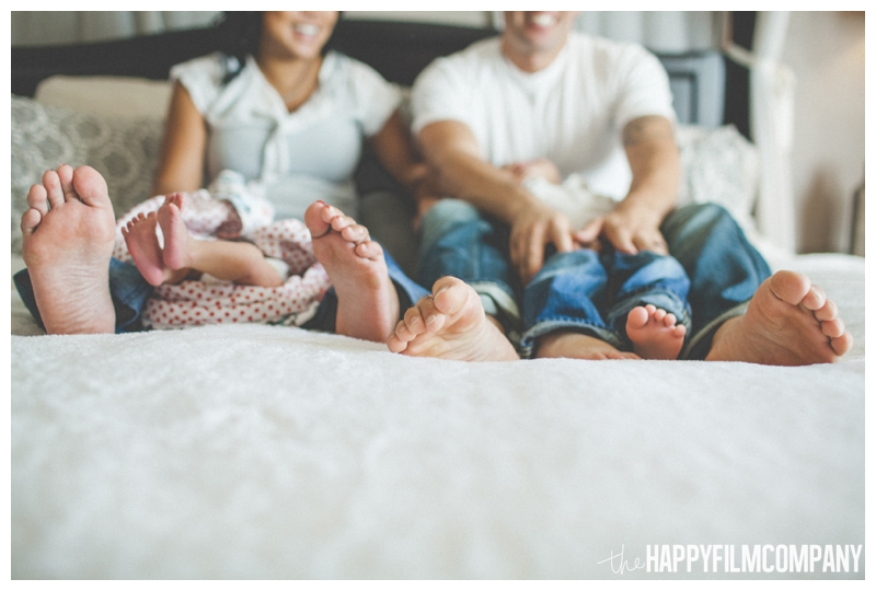 family sitting on bed feet photo  - Natural Seattle Newborn Photography - the Happy Film Company