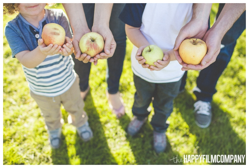 family holding apples in their hands  - Seattle Family Apple Picking Photo Shoot - the Happy Film Company