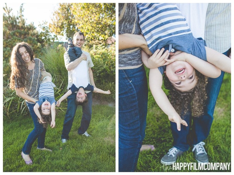 parents swinging kids upside down  - Seattle Family Apple Picking Photo Shoot - the Happy Film Company