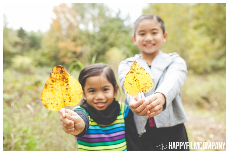 girls holding leaves  - Seattle Autumn Family Photos — Playing in the Leaves at Black River Riparian Forest and Wetland - the Happy Film Company