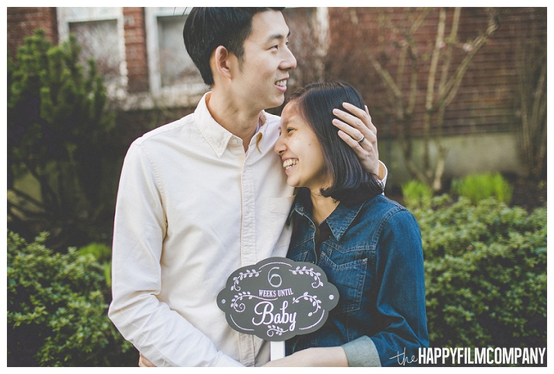 couple holding chalkboard pregnancy announcement sign kissing head  - the Happy Film Company - Seattle Maternity Photography