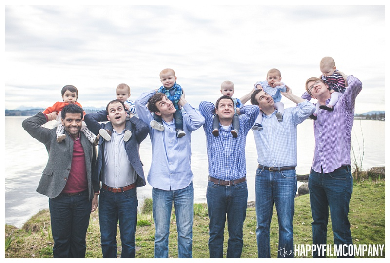 group of dads with babies on shoulders at matthews beach seattle - the Happy Film Company - Seattle PEPS Group Photo Shoot