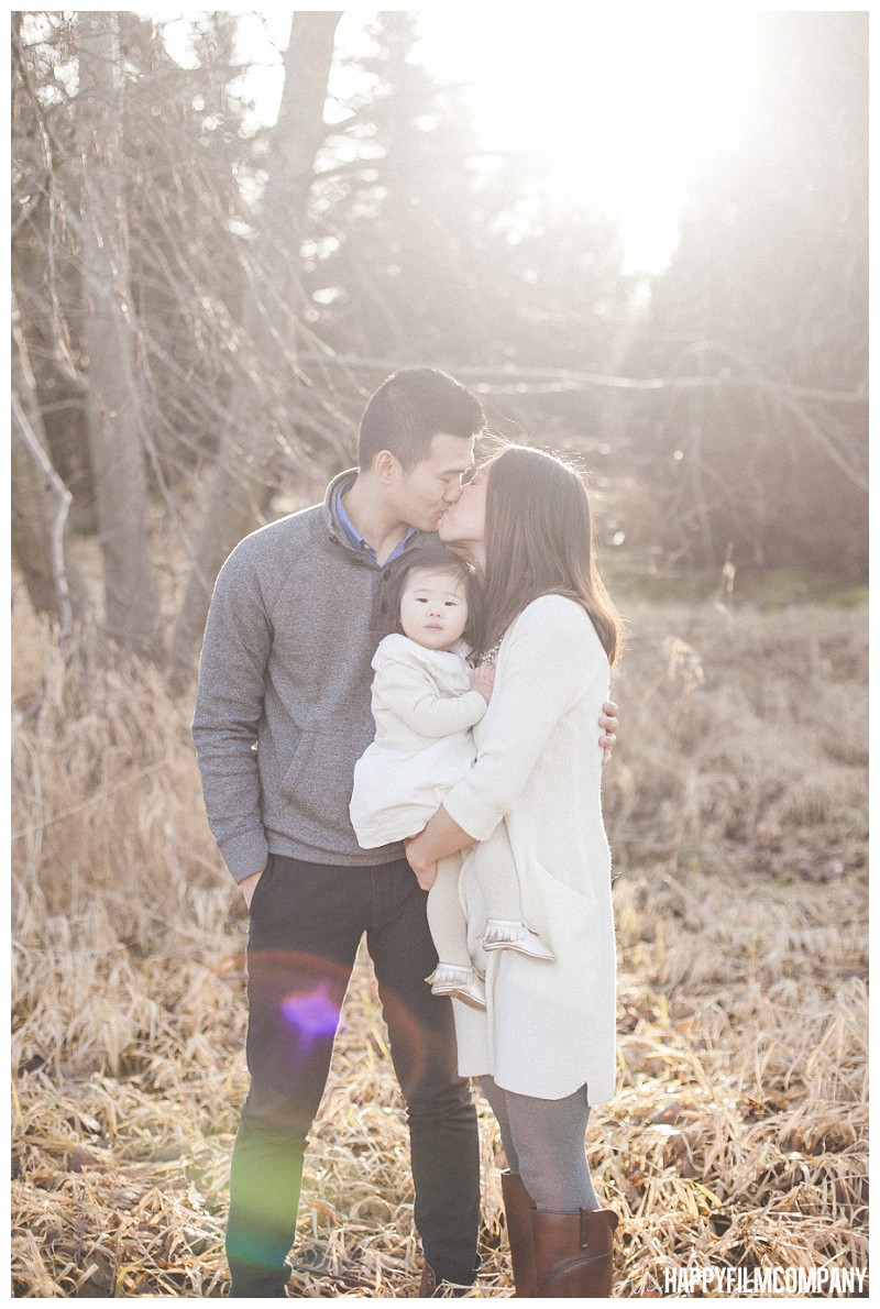 Mom and dad kissing with cute baby girl- the Happy Film Company - Should I book my Seattle family photo shoot at Golden Hour?