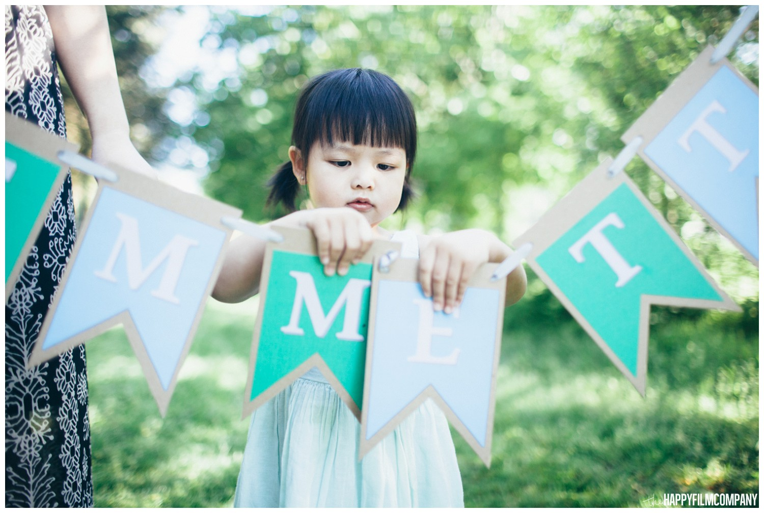 Little girl helping mom and dad holding their props for the photoshoot - the Happy Film Company - Seattle Family  Photography