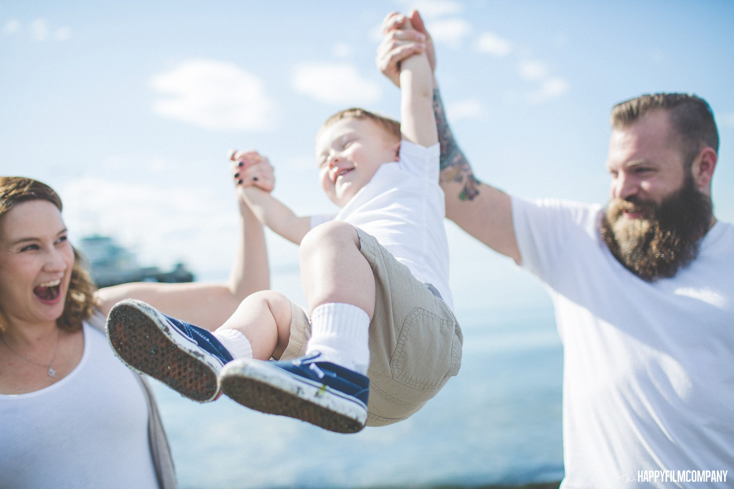 Mom and Dad lifting their son in the air - the Happy Film Company - Seattle Family Photos