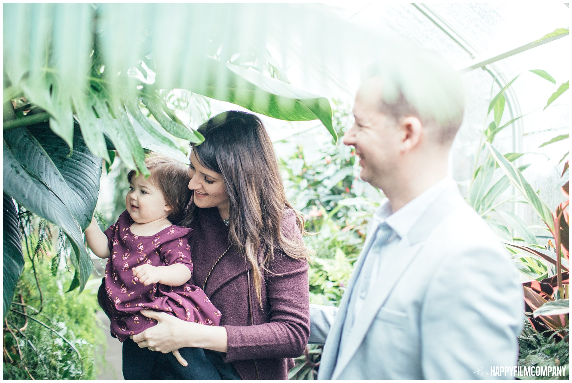 the Happy Film Company - Seattle Family Photos - Volunteer Park Conservatory - family standing underneath banana plant