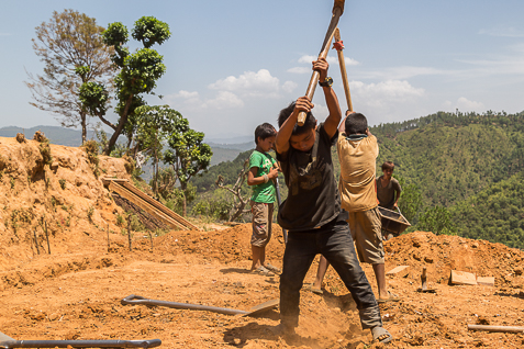 Two young boys helping dig trenches for their house in Sipapokhare.