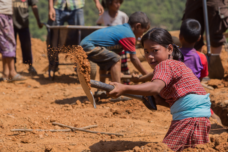 One of the many hard working children helping to rebuild this village. During breaks, her and her friends would sing songs for us.