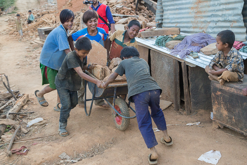Children from the village recovering usable stones from damaged houses.