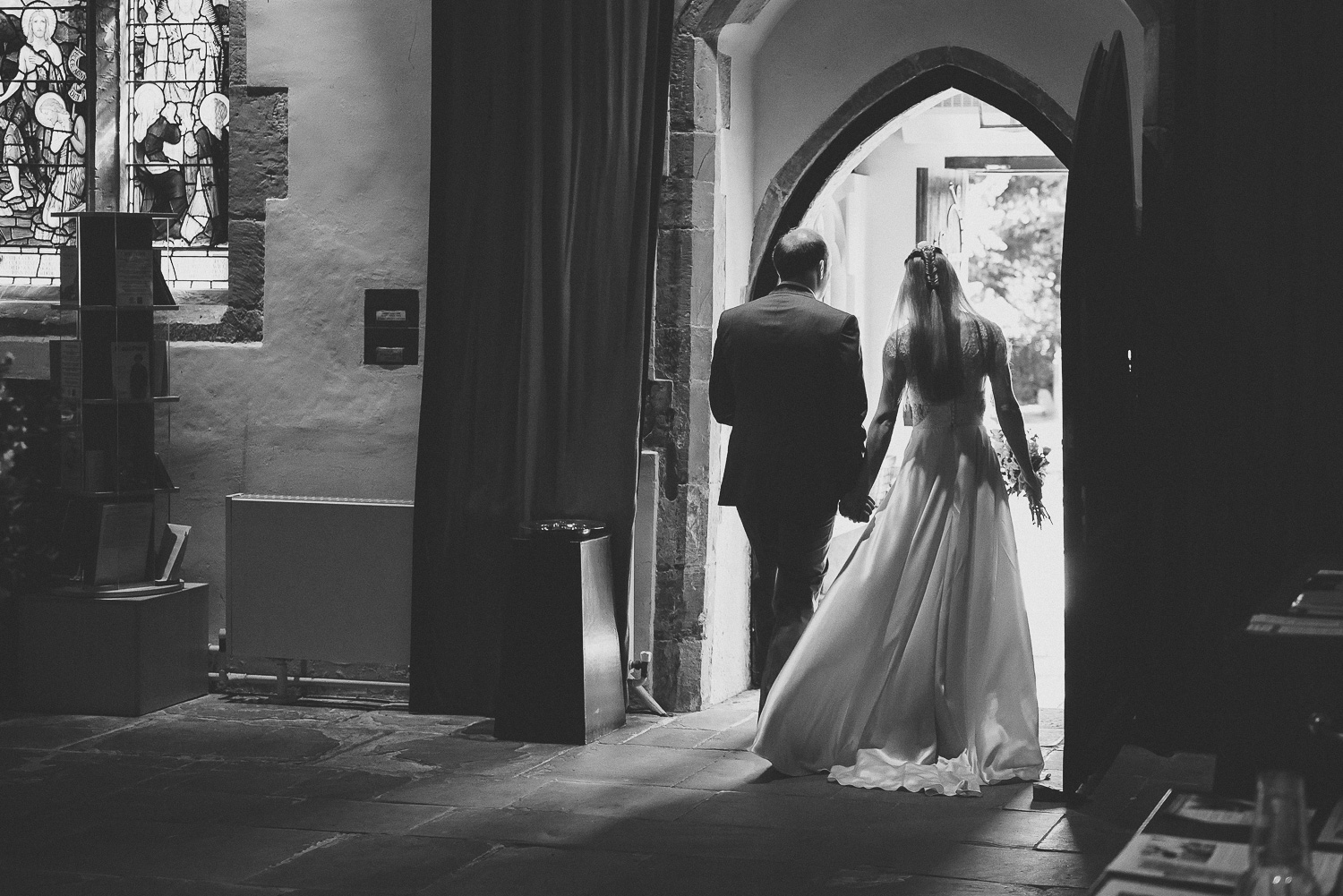 black and white wedding picture of bride and groom leaving old church