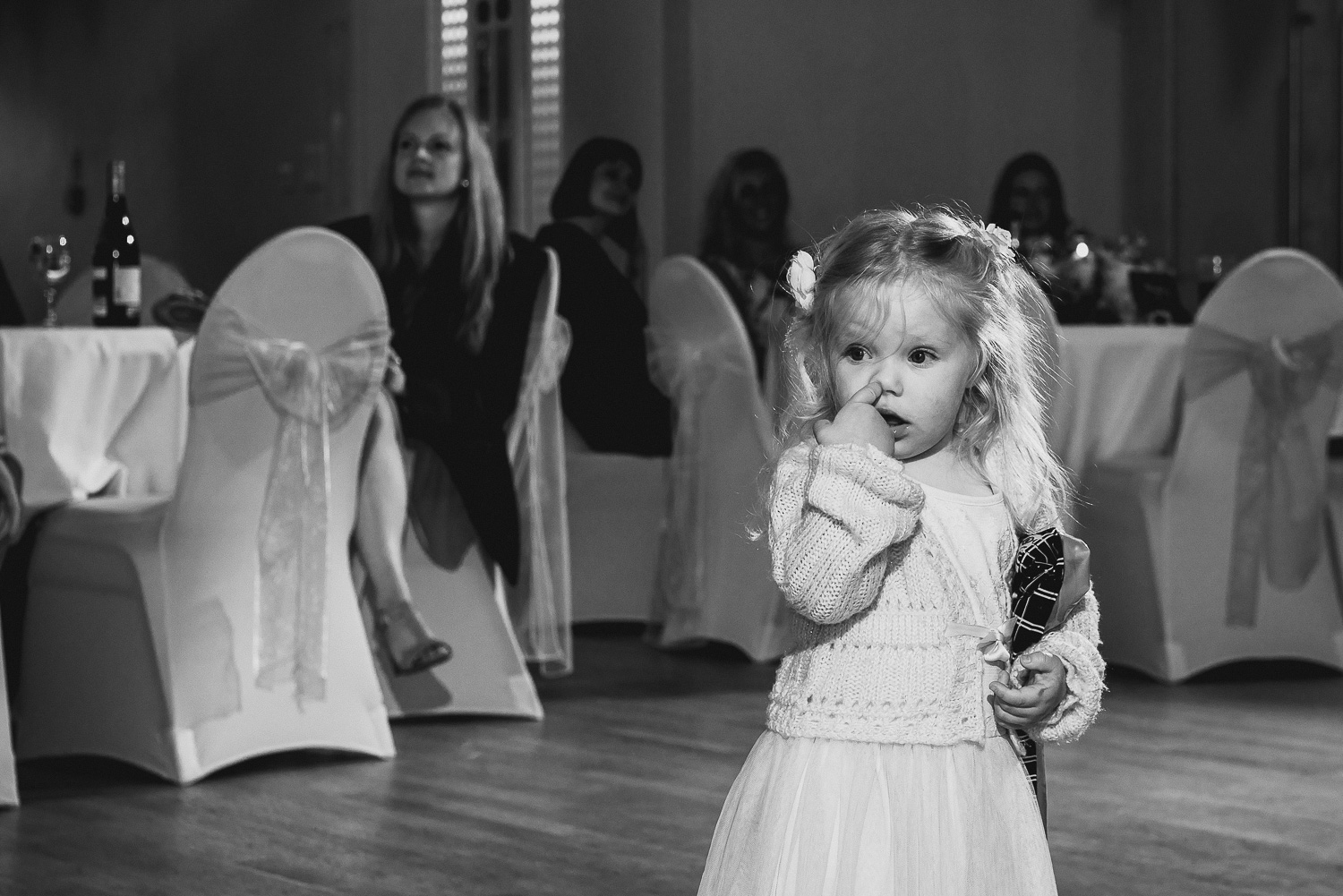 funny picture of little girl picking nose at wedding
