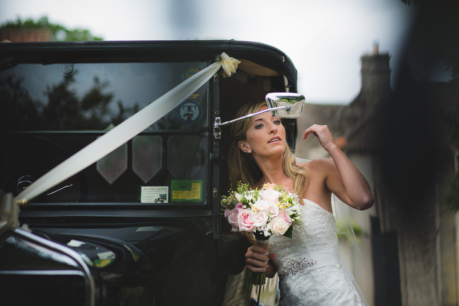 bride checking hair and make up in vintage wedding car in tetbury