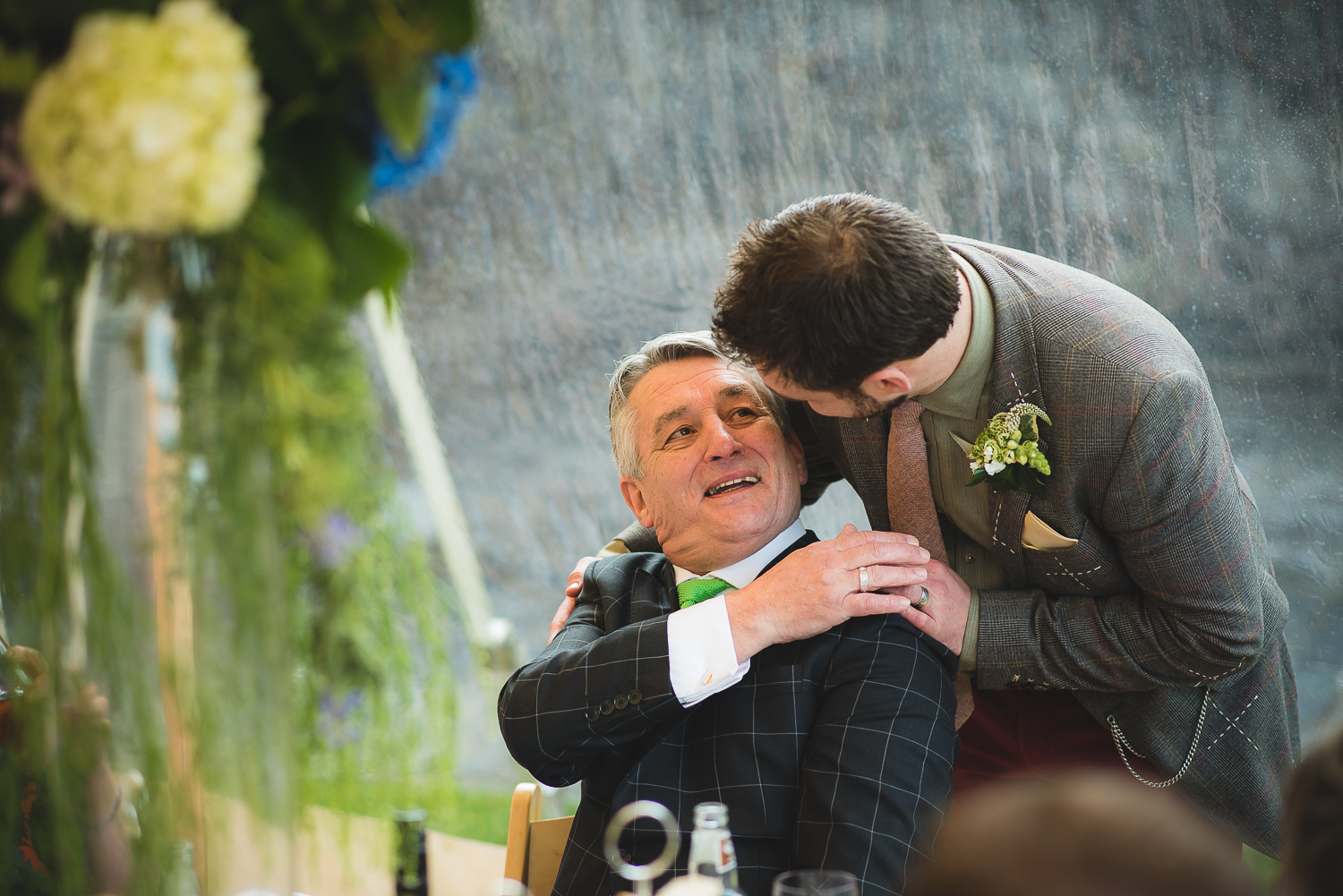 son hugs father at castle wedding in clevedon