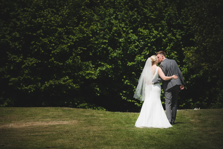 romantic moment between bride and groom walking in field