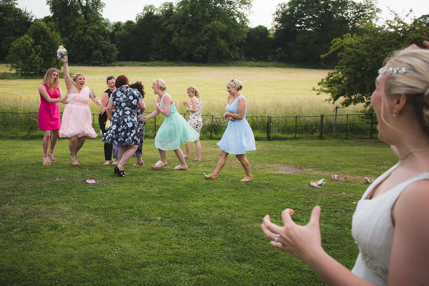 bridesmaids catching the bouquet at wedding in field in wiltshire