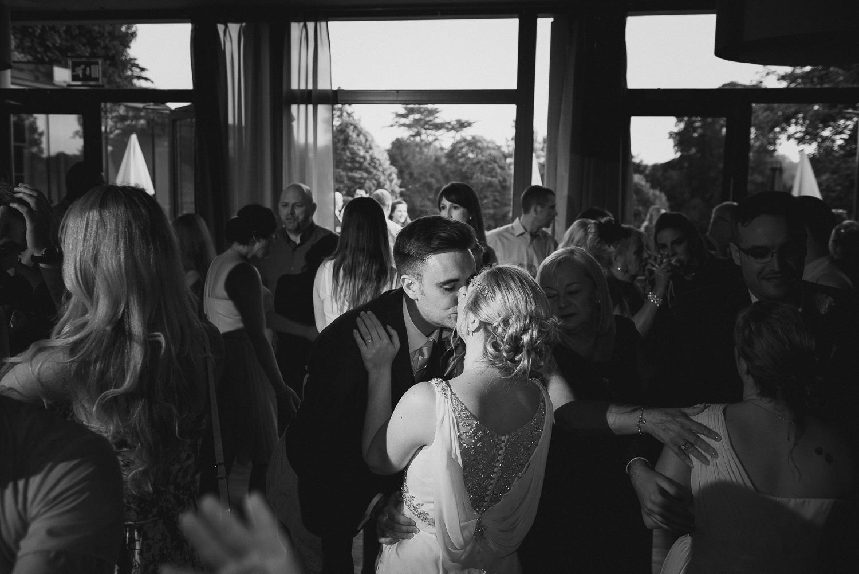 documentary wedding photo of bride and groom kissing on dancefloor