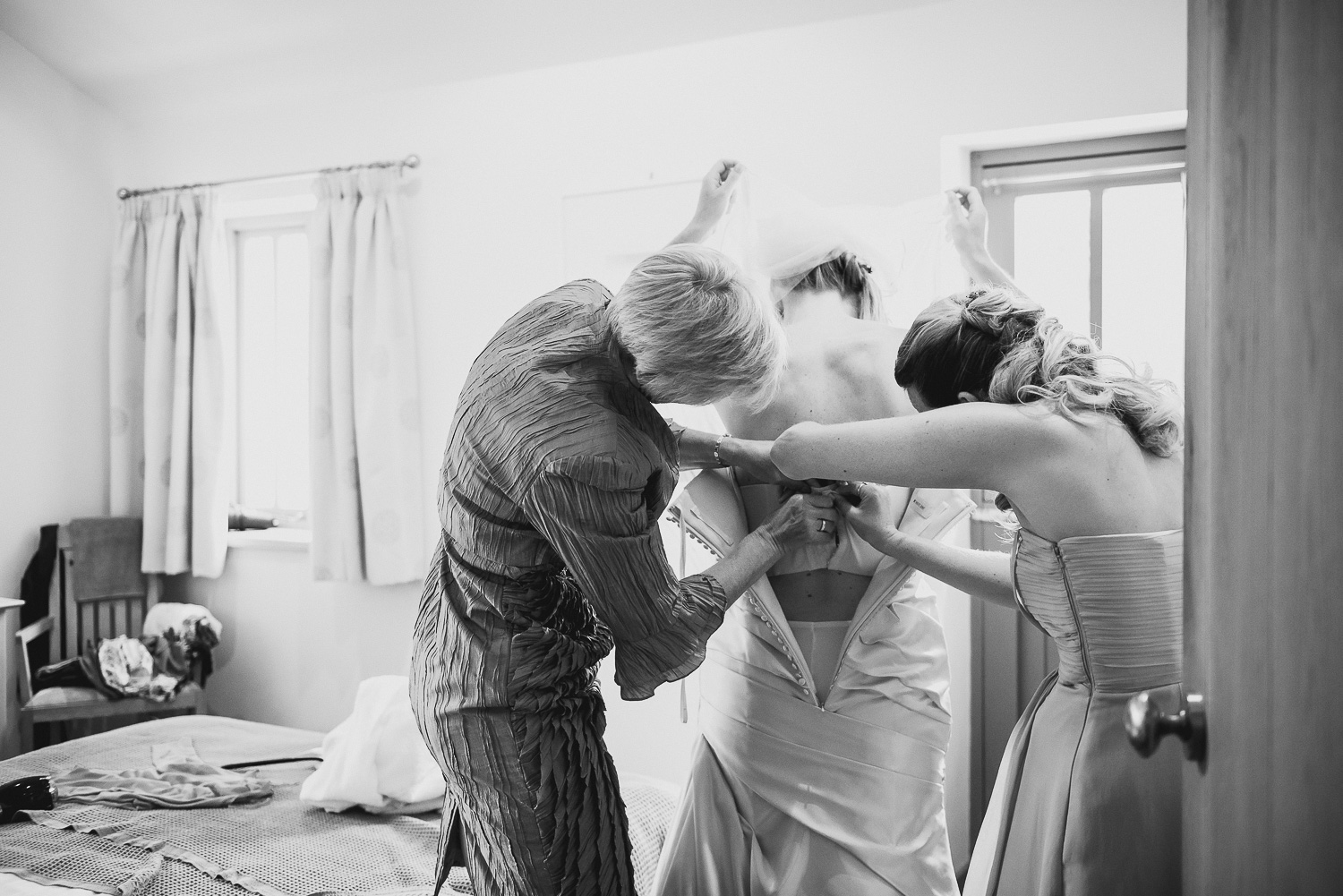 reportage photo of bride getting dressed at farm in cornwall before wedding