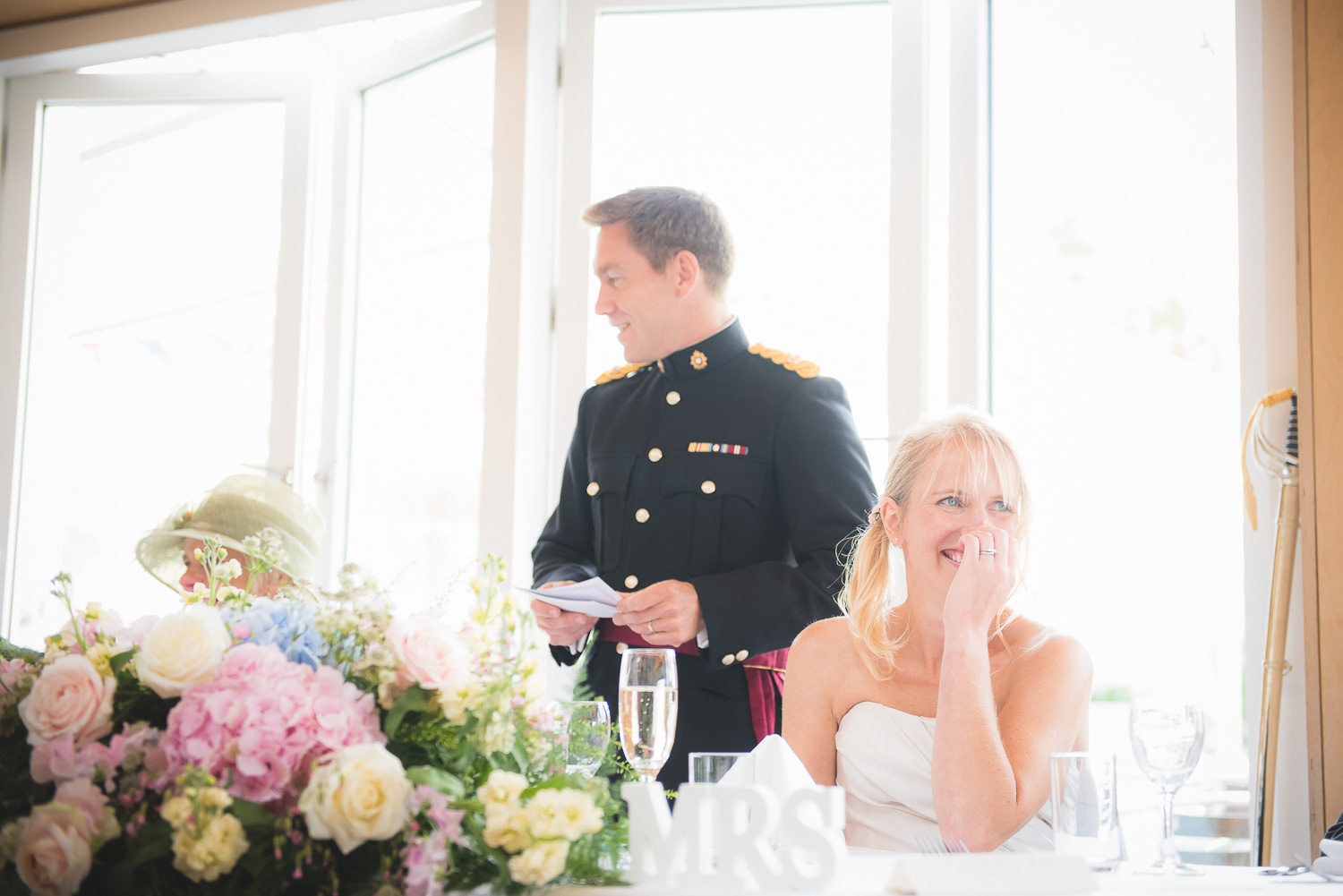 natural bride laughing during speeches at wedding