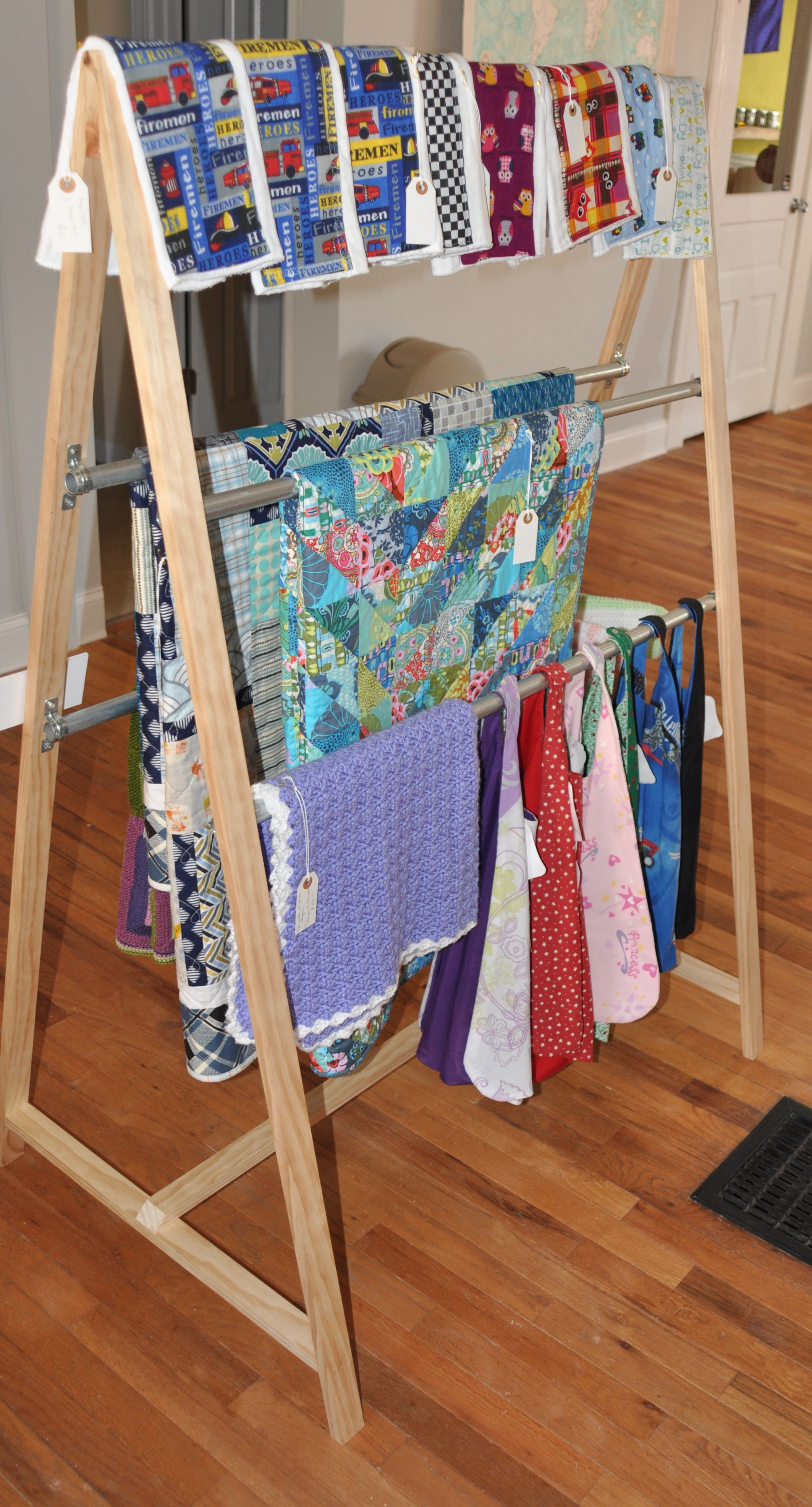 Quilts by Heather Givans and Melissa Ness Hauger; lap blanket by Ravynn M. Schroeder; Knitted Baby Clothes by Ravynn M. Schroeder and Shelia Schroeder; burp clothes and super hero caps by Sabrina Hull.