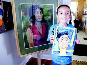 Anthony Taliaferro, 7, displays his self-portrait next to one that teacher Vanessa DeYoung created when she was in college.