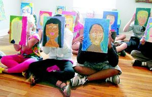 Kids show off their self-portraits at Park Place Arts after a recent class offered there.