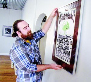 Eliot Reed, owner of Park Place Arts, hangs an exhibition of concert posters, including this Hatch 3-color screen print. Live music comes to the gallery Saturday evening with a free concert by Michael Buratto and Evan Hock.