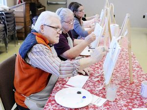 Jim Knotts paints the sky around a moon in his winter landscape during a class by Park Place Arts at Mounds State Park on Saturday. The class was so popular that a second was added.