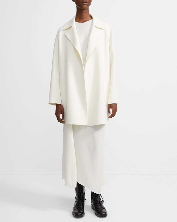 An austere and spectral white coat to take you from fall to winter, a striking black dress replete with pleats and sleeves for any and all occasions (just change the footwear).