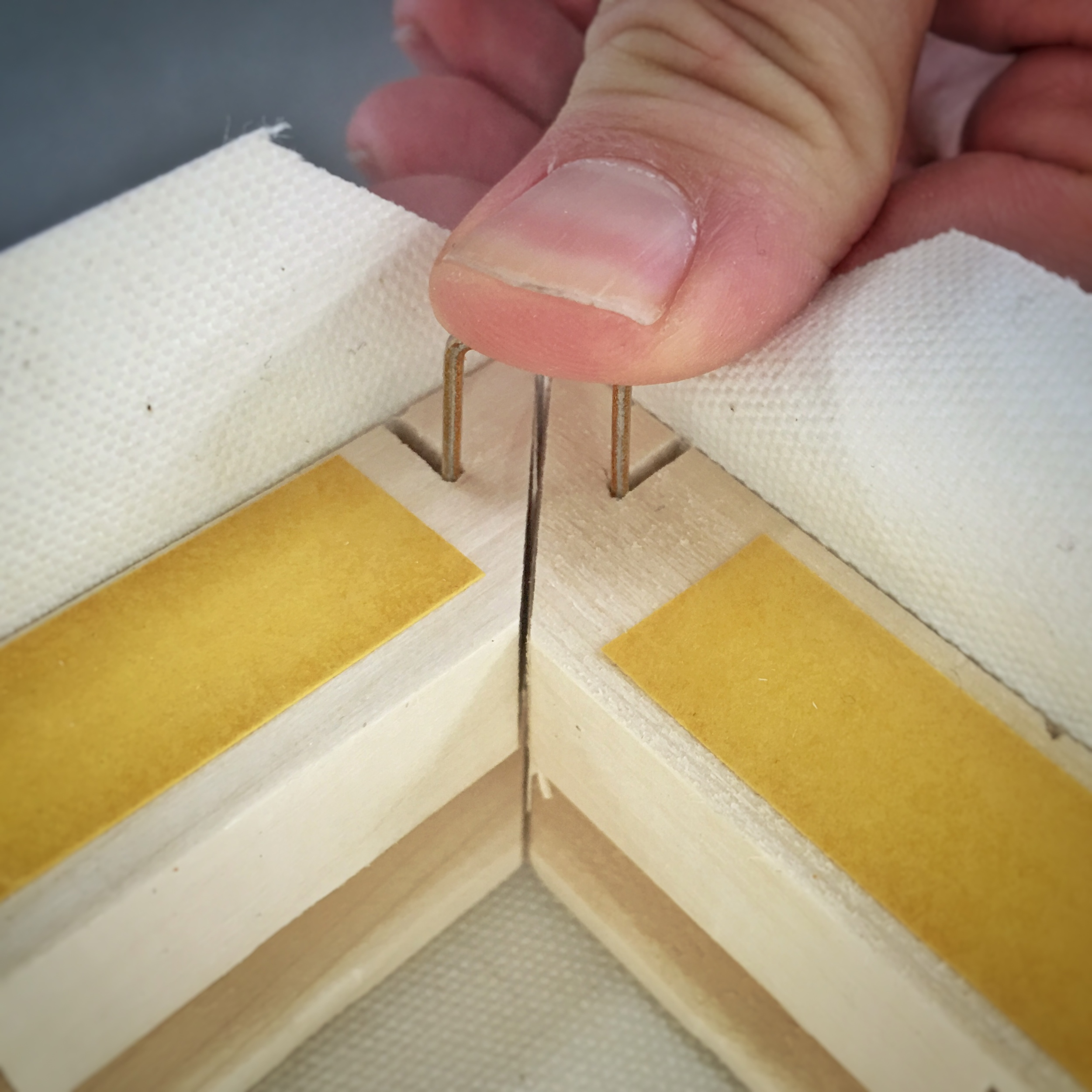U shaped fasteners allow the canvas to fold into the miter of the stretcher frame creating neat and perfectly folded corners.
