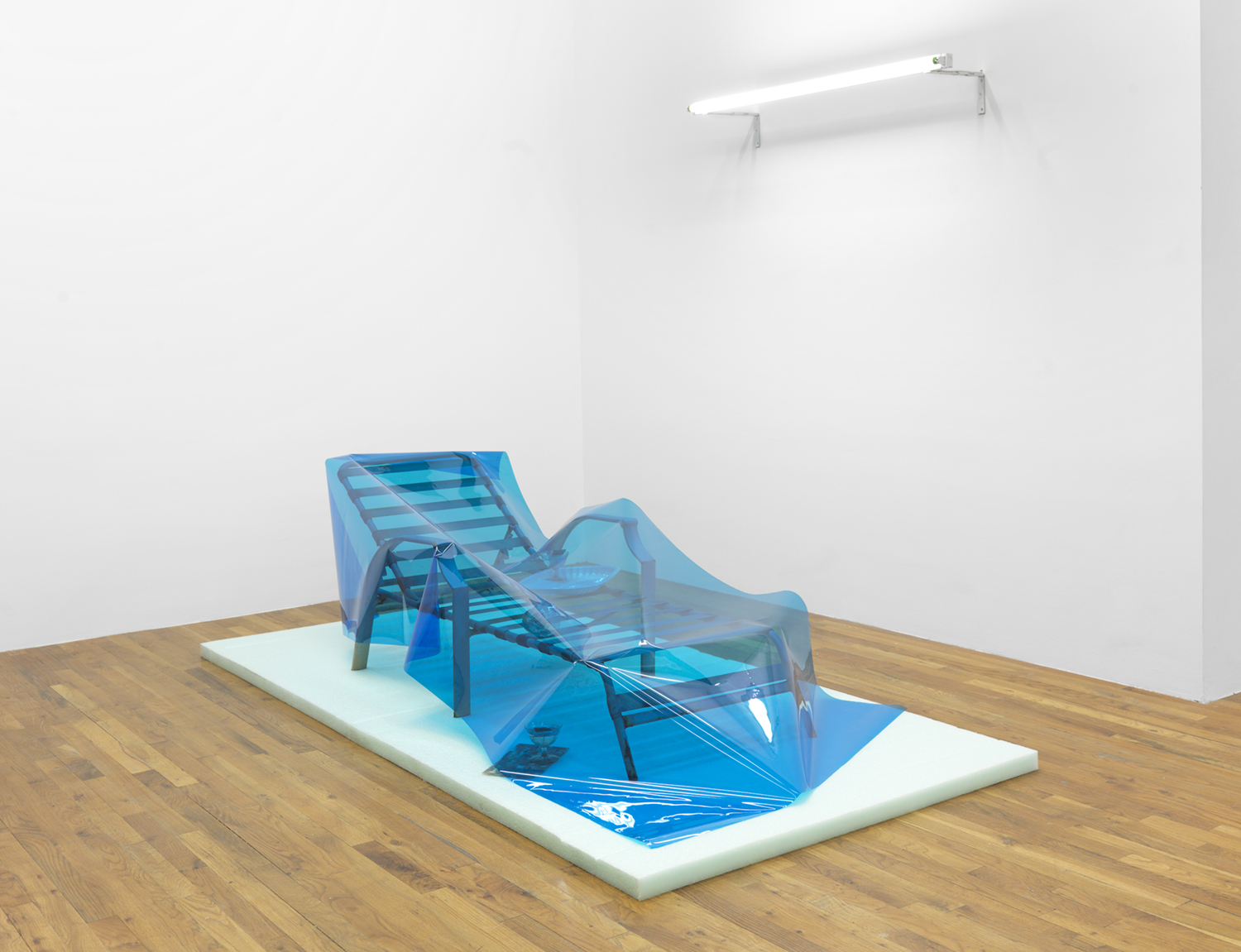 Condo Glut  2014 Packing foam, sun lounger, fluorescent light, UV lighting gel, plastic tray, glasses Dirty martini - Red Hook water, gasoline, abalone shell 26 x 97 x 48 inches