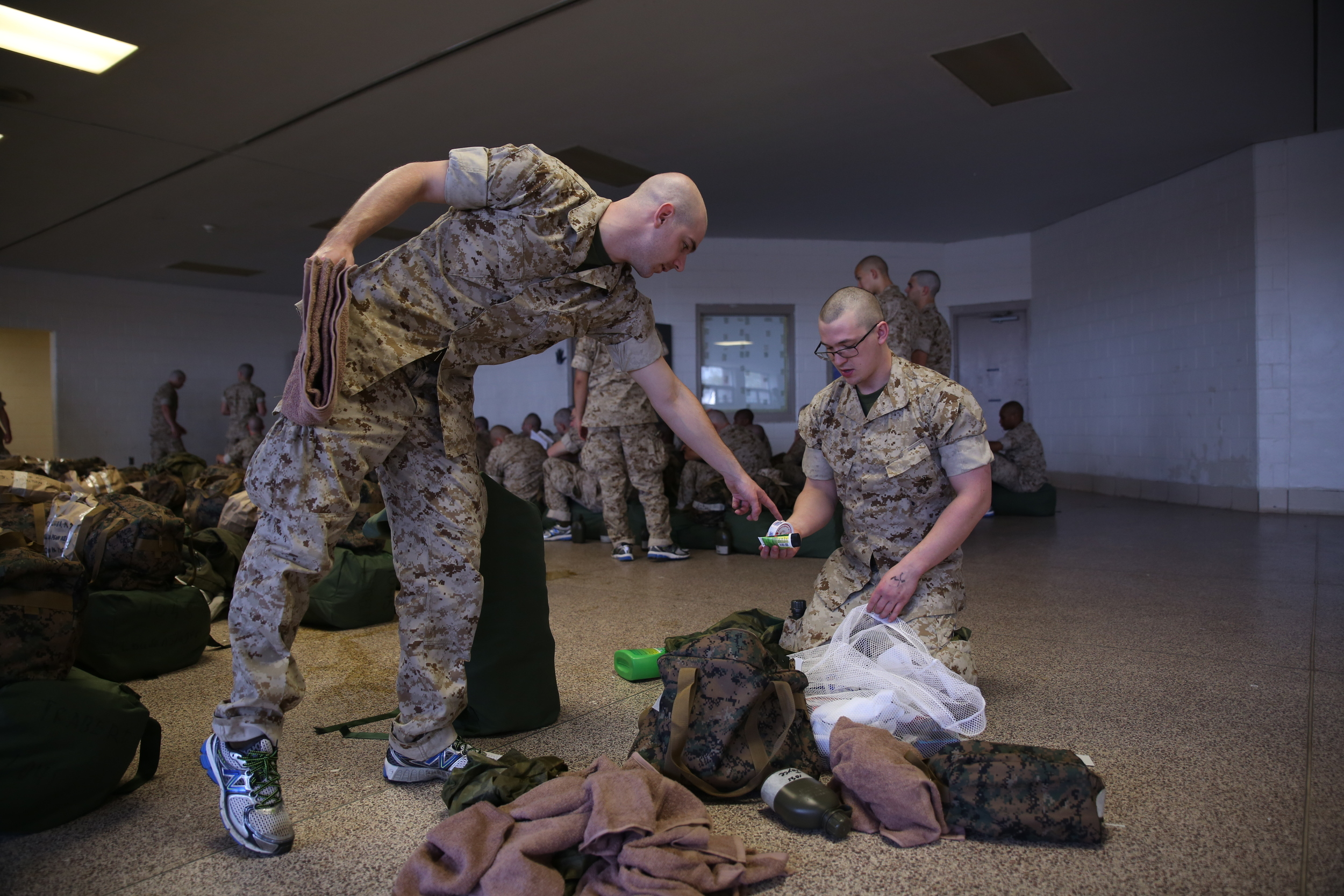 A Marine Corps recruit instructs another how to organize his things. Photo by Cpl. Octavia Davis, United States Marine Corps.