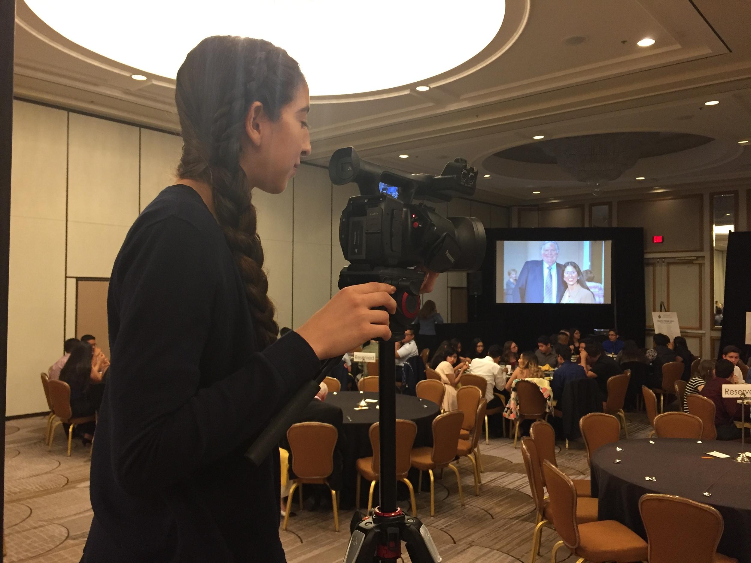DATA Junior Jennifer Reynoso operates the main camera for David Petraeus' Youth Town Hall.