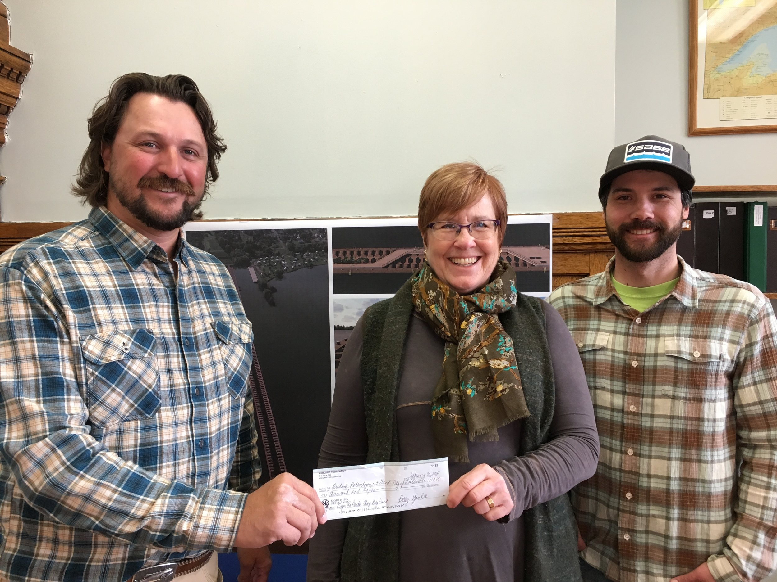 Dave Gellatly and Luke Kavajecz present Ashland Mayor Deb Lewis with a donation from the Roger Lapenter Chequamegon Bay Fund for the Ore Dock Redevelopment.