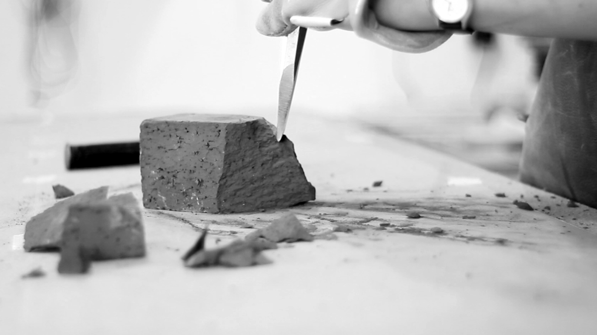 Breaking the brick with a chisel.