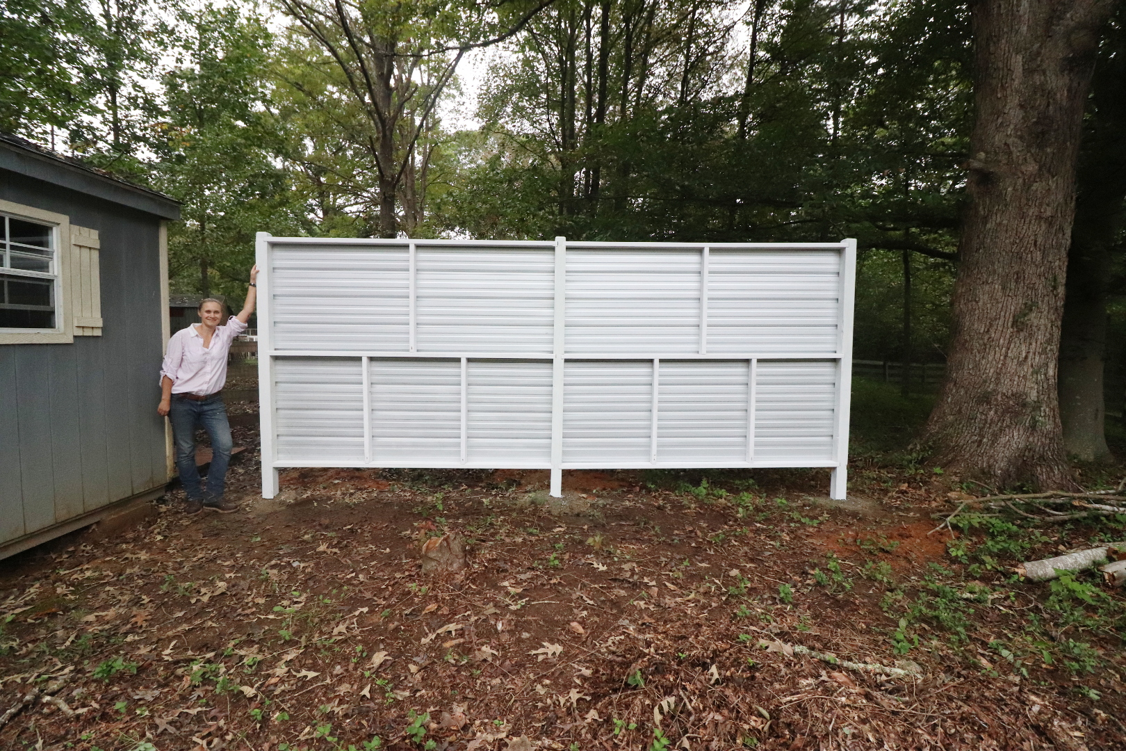 Privacy fence made with corrugated metal panels.