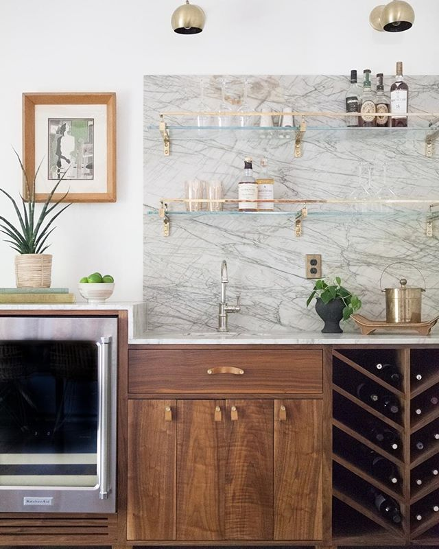 This custom bar makes it really tempting to not want to drink cocktails all day. Thankful for clients who trust us with our designs. This bar includes everything custom: cabinetry, brass and glass shelving, a stunning quartzite countertop and backsplash, and leather pulls.
