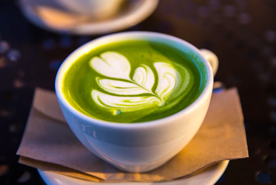 A cup of matcha latte on a white saucer with a brown napkin